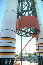Work crews install the first piece of the orange wrapping on the external tank replica.