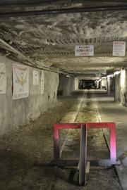 The walls of the mine are plastered with gray, spray-on material and debris is contained by nets on the ceiling and the ribs (walls) of the tunnels.
