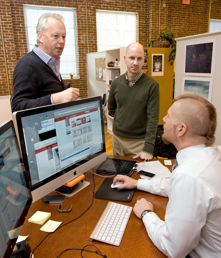 Craig Waller, left, and Dan Dooley and Shane Luitjens, seated, at Pace Communications' Greensboro office.