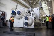 Once lowered to floor level, workers begin to prepare the 550-ton centrifugal chiller to be lowered through the floor into the mechanical room below Turbine Hall.