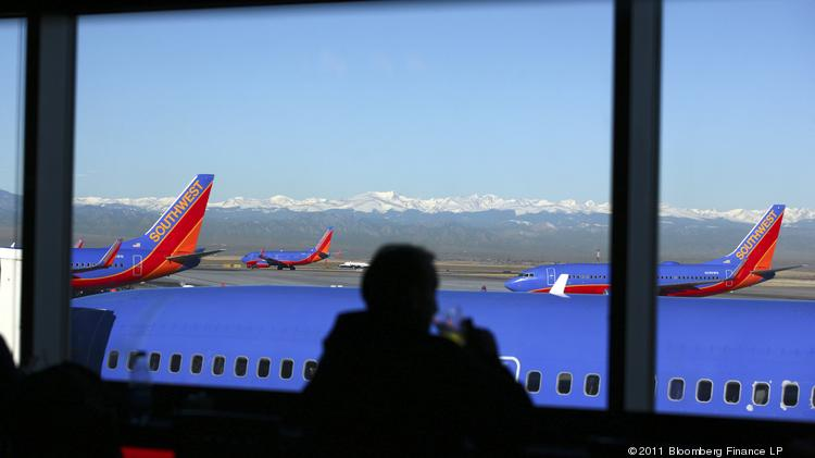 A passenger takes a drink as Southwest Airlines Co. planes taxi on the runway at Denver International Airport. Southwest has had the lowest number of per-passenger complaints filed against it for the past five years.