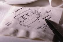female inventor drawing on a napkin