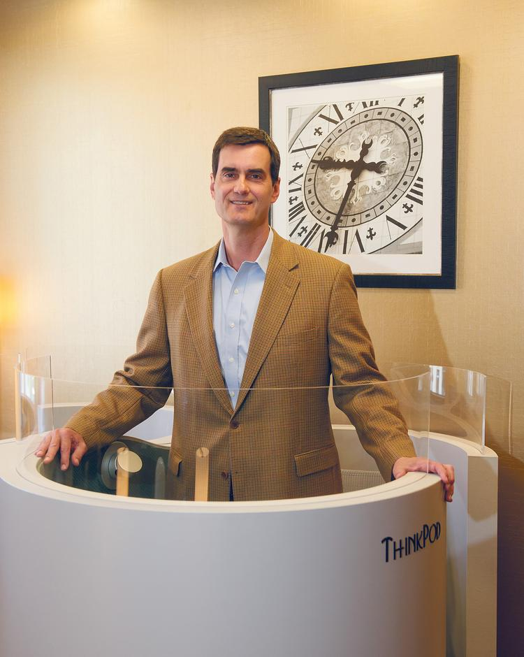 """Spencer Jones, general manager of The Regus Group's office leasing building on the Country Club Plaza, stands inside a """"ThinkPod."""""""