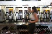 Snow & Co. manager Delaine Moltzan walks in front of a row of drink-mixing machines.