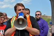 Ben Albert, an organizer with Unite Here, speaks at the protest.