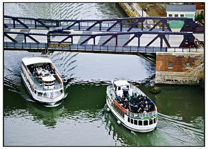 Two tour boats pass each other on the Chicago River. Mayor Emanuel has proposed hiking dock fees for such boats.
