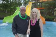 The Beach Waterpark is under the ownership of Hank, left, and Susan Woodburn. In the background is  the Cowabunga Curl, which has three brightly colored slides that empty side by side into a splash pool. The ride is 400 feet and takes an average of 45 seconds.