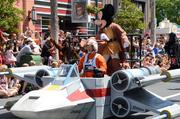 Jedi Mickey rides an X-wing Fighter parade float.