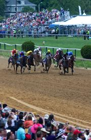 Horses race around the track in the 138th running of the Preakness Stakes at Pimlico Race Course