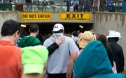 Fans on the infield head for the tunnel as rain starts to fall during Preakness at Pimlico Race Course on Saturday.