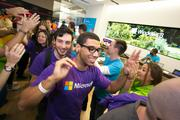 After the curtain drops, Microsoft associates welcome the first customers into the store at its grand opening in Dadeland Mall.
