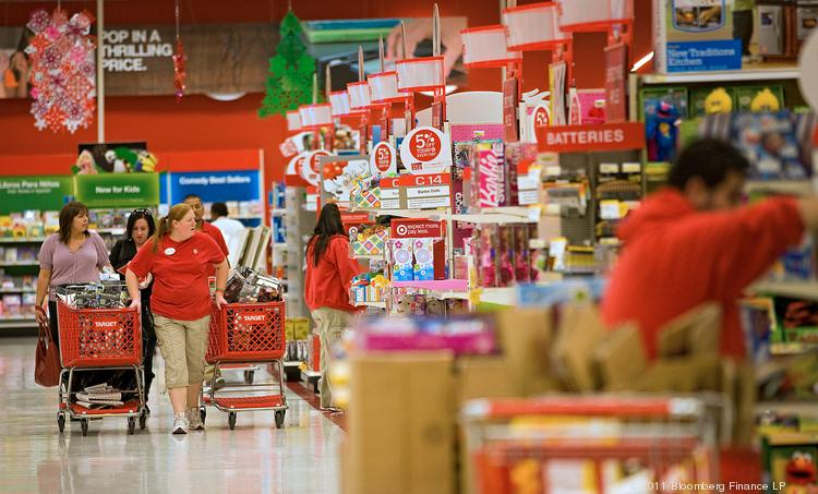 Target employees restock merchandise while customers shop at a Super Target store in the Denver area.