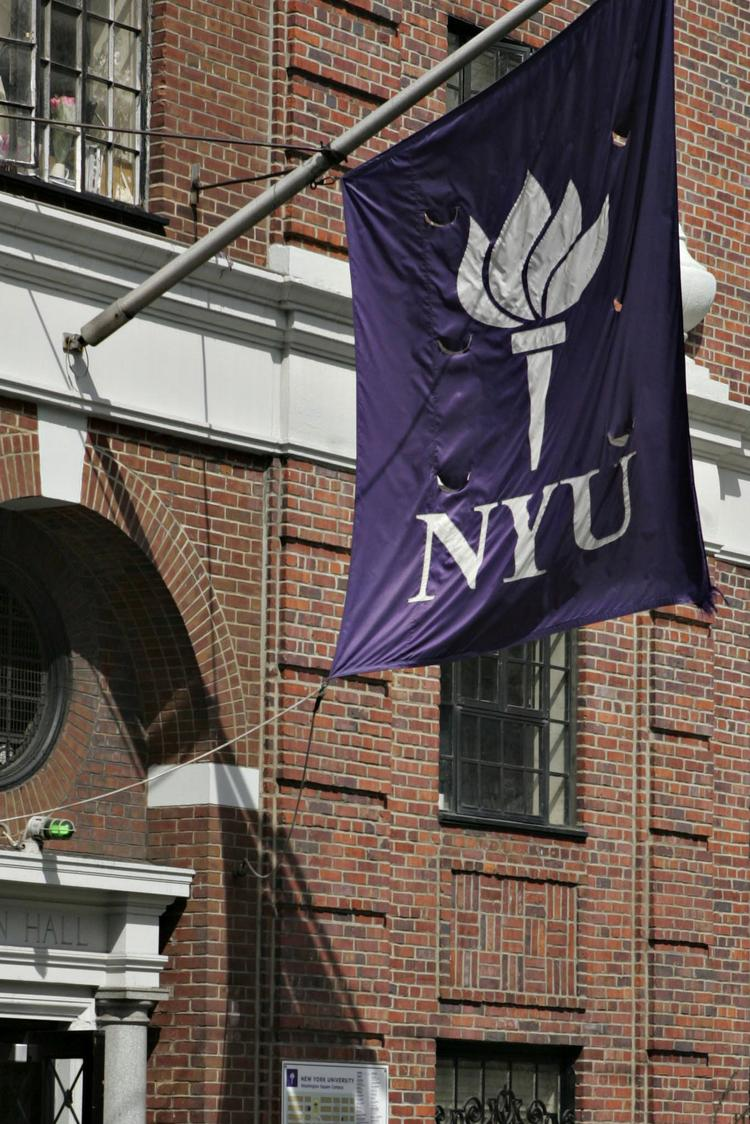 A New York University flag flies outside a campus building.