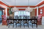 The formal dining room has dual cut-glass chandeliers, columns and bay windows.