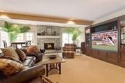 The media room in the home's lower floor also has a stone fireplace.
