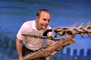 John Arie Jr. of Fun Spot with a huuuuge dinosaur skeleton in the Dino Digs gallery.