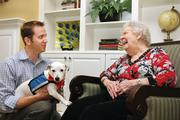 Sean McHale, president of Home Helpers, and resident Bert Harvey, 88, play with Beau at Horizon Bay Memory Care By The Bay.
