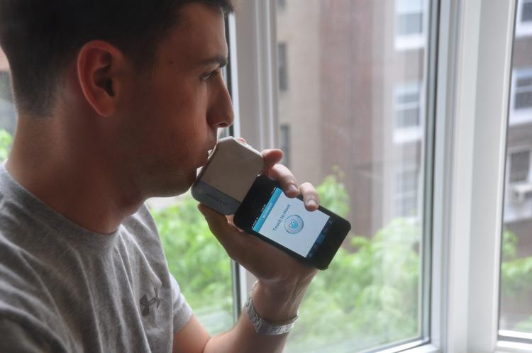 Max Koeppel, Alcohoot's CFO, demonstrates how the device works as a Breathalyzer.