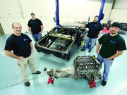 Rosedale Technical College hydraulic technolgy instructor Mark Simoneau, far left, automotive technilogy students Nick Hoovler, rear left, and James McAvoy, rear right, and automotive technology instructor Brian Winter, far right, pose with a 1969 Chevy Nova body and an engine from a 2005 Pontiac GTO. Students and staff members will use the components to build a computer-controlled 2005 Chevy Nova that will be entered in Sports Car Club of America races.