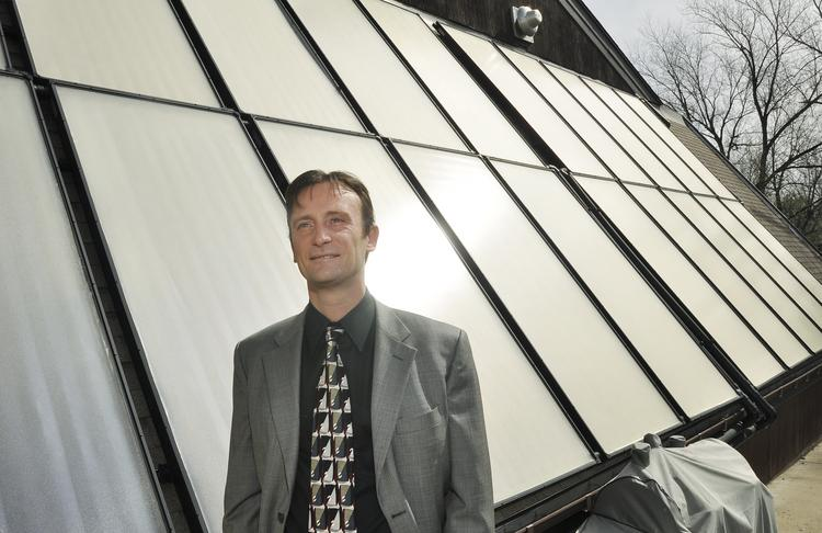 Laurent Meillon of Capitol Solar Energy stands in front of the array he installed at a business in Lakewood.