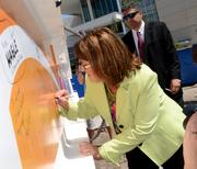 Orange County Mayor Teresa Jacobs adds her signature to the beam.