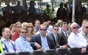 Members of the DPAC board and other guests listen to guest speakers before the beam is raised.