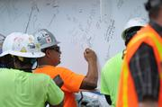 Construction crews sign their names to the beam.