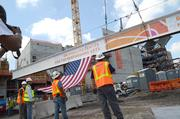 A flag is attached, and work crews watch as the beam is raised.