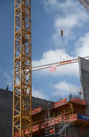 The tower crane moves the beam over its location as tower crews prepare to receive it.