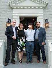 From left, Jackson Kelleher, Rachel Mitchell and Parker Watson join David Mitchell at the entrance to Mitchell's home.