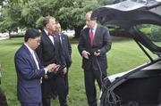 Tesla VP of Corporate and Business Development Diarmuid O'Connell shows House Speaker Thom Tillis how the charging port works.