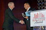Visionary Award recipient Joe Fallon, CEO and president of The Fallon Company is congratulated by Boston Business Journal Publisher Chris McIntosh at the Boston Business Journal's Best in Boston Real Estate Awards luncheon.