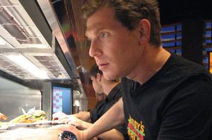 Chef Bobby Flay checks out how food is moving in the kitchen at Bobby's Burger Palace.