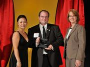 Tyler Starline accepts the 2013 Forty Under 40 award alongside Dean Joanne LI of Wright State University, the title sponsor, and DBJ Publisher Carol Clark.