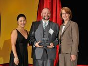 Nathan Simmons accepts the 2013 Forty Under 40 award alongside Dean Joanne LI of Wright State University, the title sponsor, and DBJ Publisher Carol Clark.