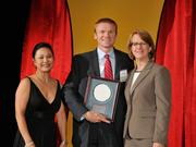 Jerad Barnett accepts the 2013 Forty Under 40 Hall of Fame induction honor alongside Dean Joanne LI of Wright State University, the title sponsor, and DBJ Publisher Carol Clark.