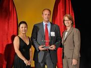 Brian Faust accepts the 2013 Forty Under 40 award alongside Dean Joanne LI of Wright State University, the title sponsor, and DBJ Publisher Carol Clark.