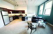 Kitchen, dining and seating areas of a one-bedroom unit model at The Brix@26 on the South Side.