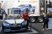 Speed Street attendees pose for a photo next to a Camaro in the Team Chevy display area.