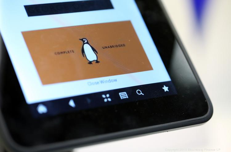 The logo of the Penguin publishing house, part of Pearson Plc, is seen on a Kindle Fire HD e-reader. Penguin reached a settlement with 33 states and private plaintiffs over e-book pricing litigation.