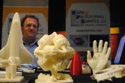 Ken Brace of Rapid Prototyping Services LLC mans his booth, which is covered with 3-D printed objects.