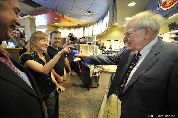 Berkshire Hathaway's Warren Buffett (right) and Dairy Queen's CEO John Gainor (left) serves Paula Talamo (center) at a Dairy Queen in Omaha, Neb., earlier this summer. Berkshire Hathaway owns Dairy Queen.  (Dave Weaver/AP Images for Dairy Queen)