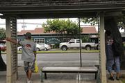 People wait at a bus stop across from the Kalapawai Cafe & Deli on Kailua Road at the entrance to Kailua town.