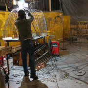 Jesse Pardun welds a wire frame for the mechanical bear that will sit on the Alaska Air float