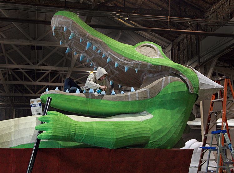 "SCi 3.2 employees Seth Williams put finishing touches on the gator for the Reser's Fine Foods float titled, ""Find Your Party Animal."""