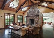 Storybook Farmhouse interior with riverstone fireplace.