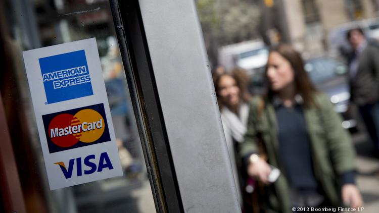 The American Express, Visa and Mastercard logos are displayed in a shop window.