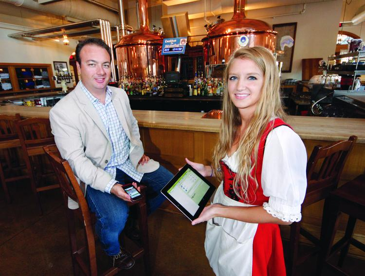 Hofbrauhaus hostess Alysia Umbaugh and NoWait CEO Robb Myer hold different versions of the NoWait restaurant tool.