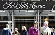Pedestrians walk outside a Saks Fifth Avenue store in New York. The company will be getting new leadership as well as new owners.