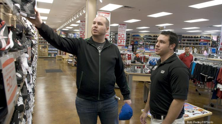 f8191a1d64ddc Hibbett Sports manager Josh Knighten helps Matt Laymon while he looks for  hats and shoes at